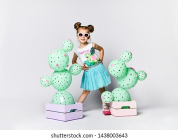 Young blonde girl posing on a background on a fictional cactus in a wooden box of pastel pink. The flowers are made of balloons with pink flowers and painted spines.