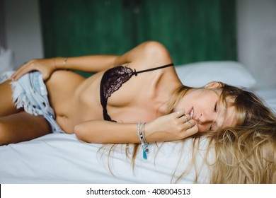 young blonde girl in blonde silk underwear and denim shorts, hipster, lying on a bed at home in the bathroom, posing, sexy body, tan, athletic figure, fitness ,outdoor portrait, close up, body