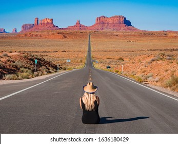 Young blonde girl sits in the center of Forrest Gump Point Road to Monument Valley, region of Colorado Plateau buttes Arizona Utah border