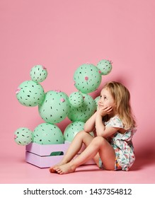 young blonde girl is sitting sitting down near a fictional cactus in a pastel pink wooden box. The flowers are made of balloons with pink flowers and painted spines.