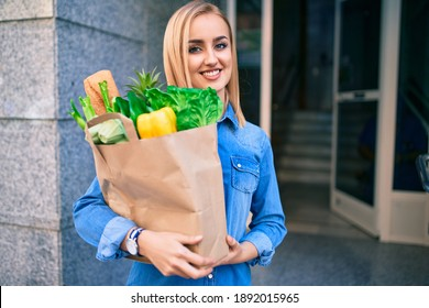 Young blonde girl smiling happy holding groceries paper bag standing at the city.