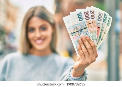 Young blonde girl smiling happy holding czech koruna banknotes at the city. - Shutterstock ID 1908782635