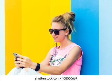 young blonde girl in sunglasses posing sitting on the floor near a colored wall, my phone and smart watch, girl in sneakers and jeans,works, photos,social networks,facebook, instagram,outdoor portrait