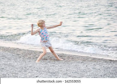 A young blonde girl throwing a rock to skip rocks at Centennial Beach on Lake Ontario in Hamilton, Ontario, Canada, at dusk.