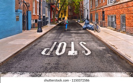 Young blonde girl walks on an empty road in Greenwich village with the inscription and STOP sign on asphalt and old colored buildings around, Manhattan New York, USA