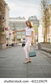 young blonde girl walks through the streets of the city. center of Moscow. Summer hot sunny day. girl dressed in pink pants and white topic