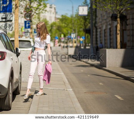d9f8c769e1 young blonde girl walks through the streets of the city. center of Moscow.  Summer. View Preview