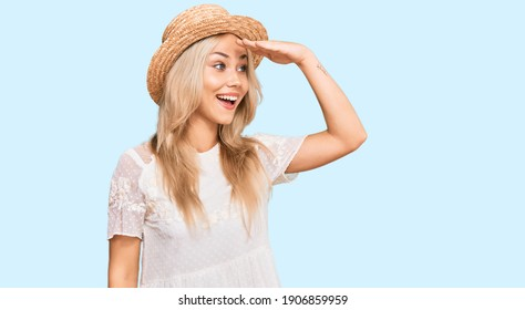 Young blonde girl wearing summer hat very happy and smiling looking far away with hand over head. searching concept.