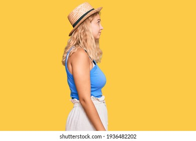 Young blonde girl wearing summer hat looking to side, relax profile pose with natural face with confident smile.