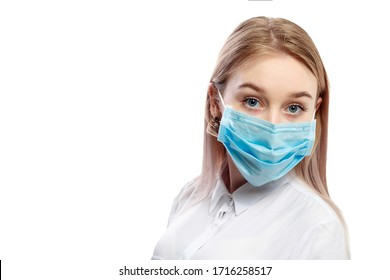young blonde girl in a white blouse and a medical mask on a white background.