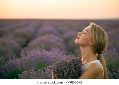 Young Blonde Girl in White Dress in Lavender Field at Sunset