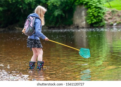 Young blonde girl wish fishing net wading into river
