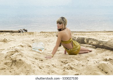 young blonde in gold dress on the sand at the beach near the sea with a goldfish in an aquarium
