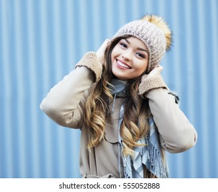Young blonde happy smiling surprised girl in beige coat and warm hat and scarf outdoor closeup portrait. Cold outside. Winter clothes