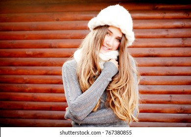 Young blonde happy smiling surprised girl in grey knitted sweater and white warm hat and scarf outdoor closeup portrait. Cold outside. Winter clothes. Female model with copy space. Christmas.