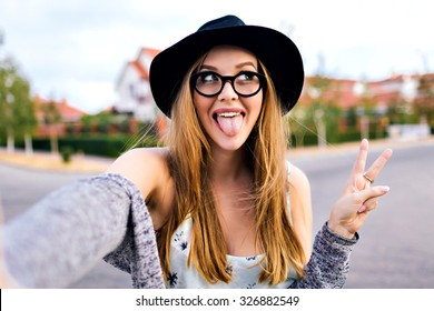 Young blonde hipster woman, making selfie, showing tongue, funny face, posing at countryside at autumn day, stylish hat and clear sunglasses.