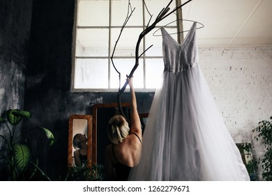 Young blonde hipster woman takes off her wedding dress from the peg standing in the loft