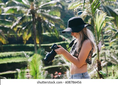 Young blonde hipster woman wearing black hat and jeans travelling around Asia, enjoying green rice terrace view, wanderlust blogger, Bali luxury vacation, taking pictures with her camera