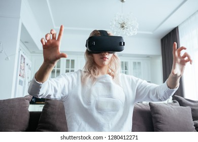 Young blonde at home with a modern design puts on virtual reality glasses