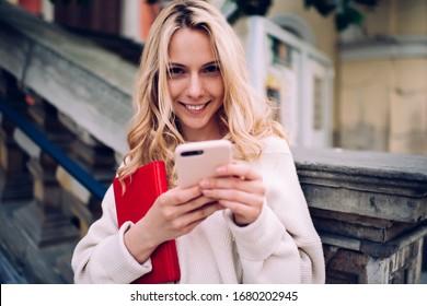 Junge blonde Dame in zwanglosem Tragen surfen in sozialen Medien und schauen Kamera an, während sie auf Treppen sitzen und sich auf Steineisen stützen