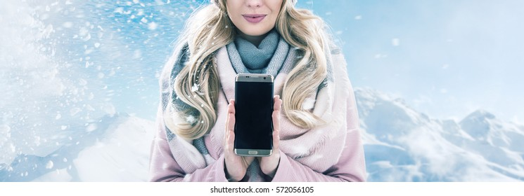 Young blonde lady holding a smartphone on a winter type background