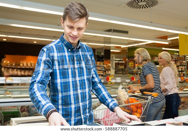 young blonde man chooses products in the supermarket