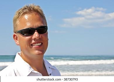 Young blonde man having fun at the beach