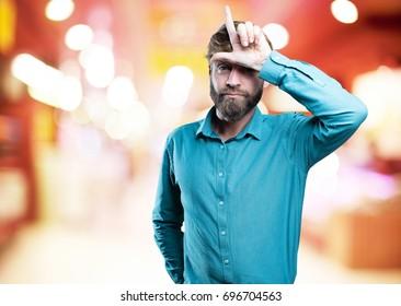 young blonde man loser sign. sad expression