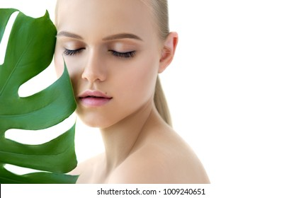 Young  blonde model with close eyes and green leaf, isolated on white. Beauty natural make up. Spa and wellness and skin care concept.  Close up, selective focus, copy space.