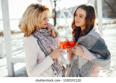 young blonde mom with her grown up daughter in the spring park with mulledwine