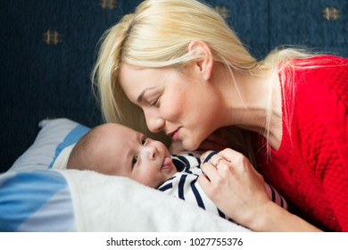 Young blonde mom playing with her baby.