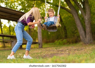 Young blonde mom shakes her little son on a swing in a green park. Happy childhood