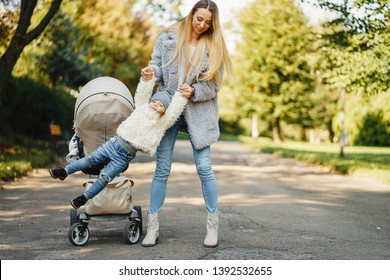 young blonde mother walking and playing with her toddler daughter and pushing a stroller through the park on a sunny day