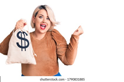 Young blonde plus size woman holding money bag with dollar symbol screaming proud, celebrating victory and success very excited with raised arms