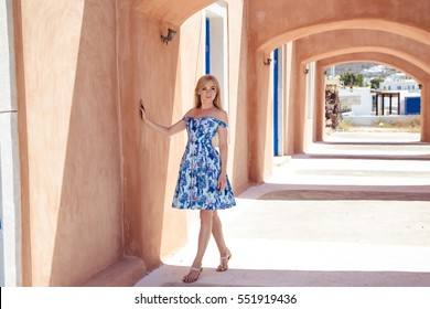 Young blonde pretty woman in a white and blue dress over Mediterranean view