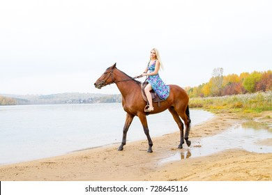 Young blonde riding a horse jumps along the shore of the bay