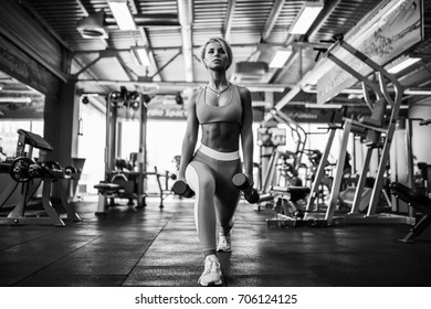 Young blonde sexy girl in the gym doing squat with dumbbells.