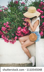 Young blonde slim girl in sunhat, lace top and denim shorts with straw round bag sitting on white parapet smelling blooming pink flowers of oleander tree at seaside. Summer travel lifestyle concept