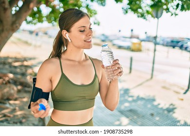 Young blonde sportswoman doing exercise drinking bottle of water at the city.