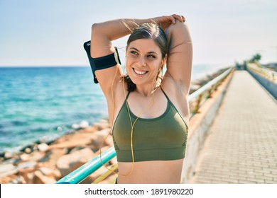 Young blonde sportswoman wearing sportswear stretching at the  promenade.