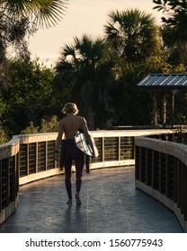 Young blonde surfer holding his surfboard walks down the New Smyrna Dunes boardwalk to the beach at sunrise.