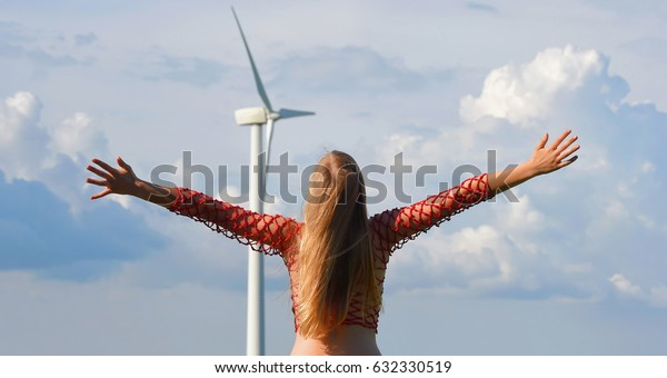 A young blonde teenage girl dressed in red admires a modern day wind turbine standing between her and a wheat field.