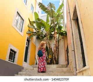 Young blonde tourist wearing a hat and generic sundress is exploring southern european city streets