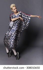 Young blonde transgender woman model in long blue pattern dress, white half-hose and black sneakers, with creative make up: red lips and red eyebrows. Neutral grey background. Studio