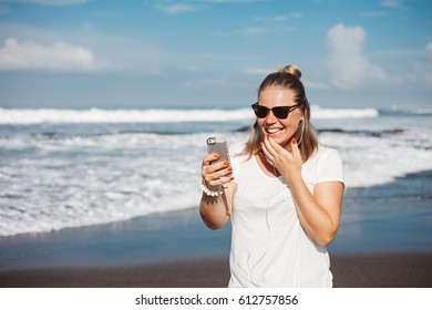 Young blonde travelling woman taking pictures with her smartphone on the beach during vacation. White t-shirt and jeans. Blogger, travel and leisure, globetrotter. Online translation, video chat