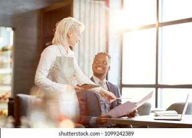 Young blonde waitress recommending businessman their special course from menu in cafe