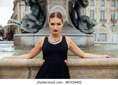 Young blonde wears formal black dress by a fountain.