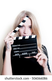 Young blonde woman actress in black shirt posing for audition with movie clapper board, looking at camera