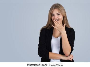 Young blonde woman amazed, copyspace, isolated on grey