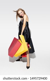 Young blonde woman in black dress shopping on white background. Attractive caucasian female model. Finance, black friday, cyber monday, sales, autumn concept. Copyspace. Smiling, laughting.